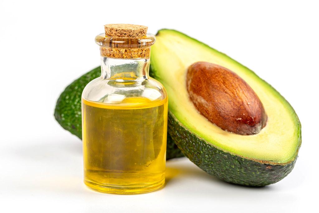 Bottle of avocado essential oil with fresh half avocado, close up