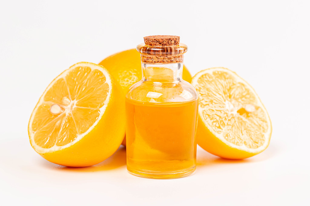 Bottle of essential oil from lemon and fresh ripe lemons on white