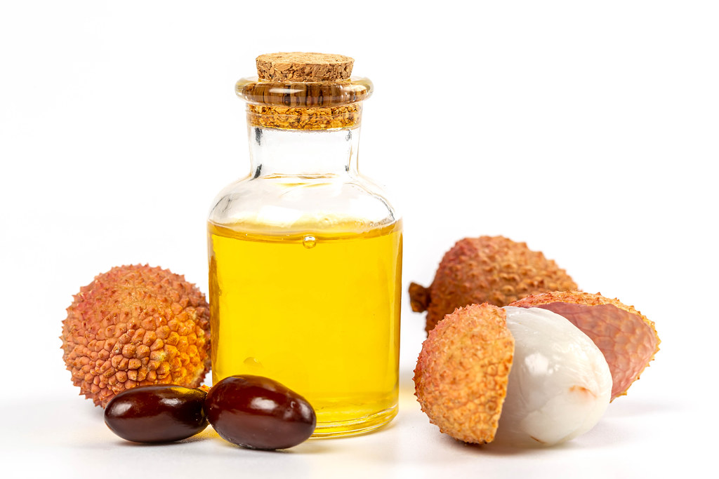 Bottle of lychee essential oil with fresh fruits lychee