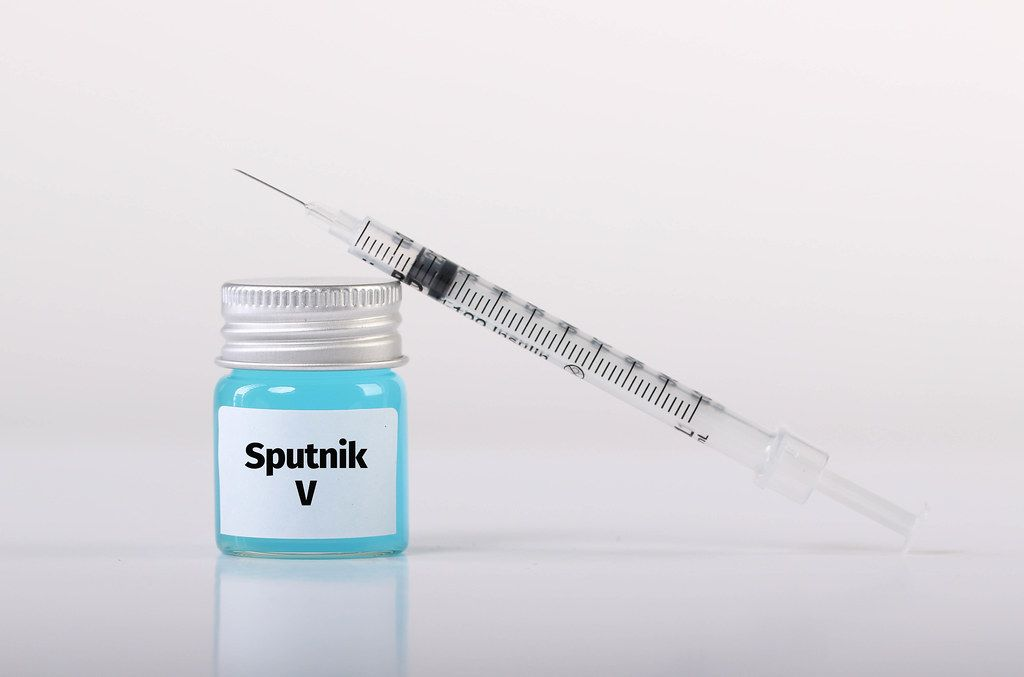 Bottle with Sputnik V vaccine and syringe on white background