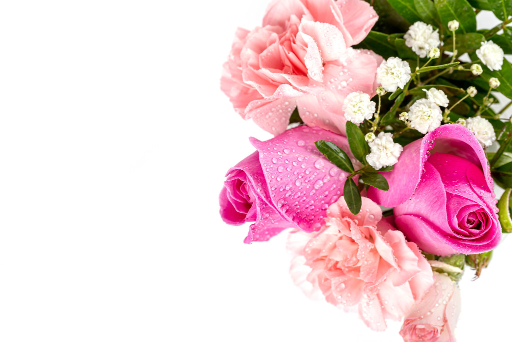 Bouquet of flowers - roses and carnations with water drops on a white background, top view
