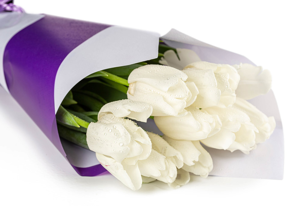 Bouquet of white tulips in a purple and white package