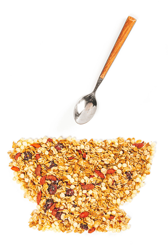 Bowl made of oatmeal with dried berries and seeds on a white background with a spoon, top view