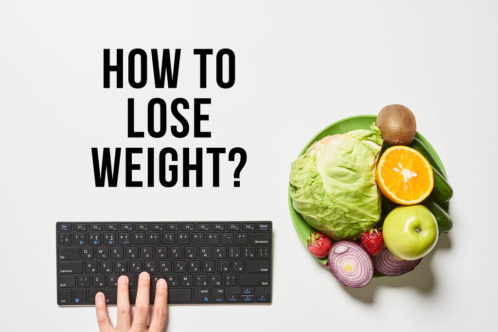 Bowl of fruits and vegetables, and hand of person typing on computer keyboard with text - how to lose weight