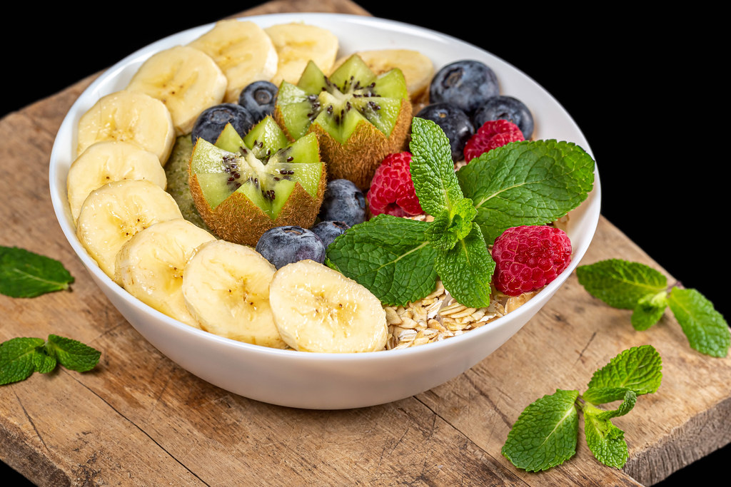 Bowl of oatmeal with blueberries, banana, kiwi, raspberries and mint on wooden kitchen board, close-up