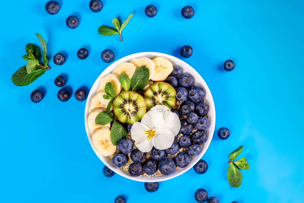 Bowl of oatmeal with blueberry, banana, kiwi edible flower blossom on blue background with fresh mint leaves, top view
