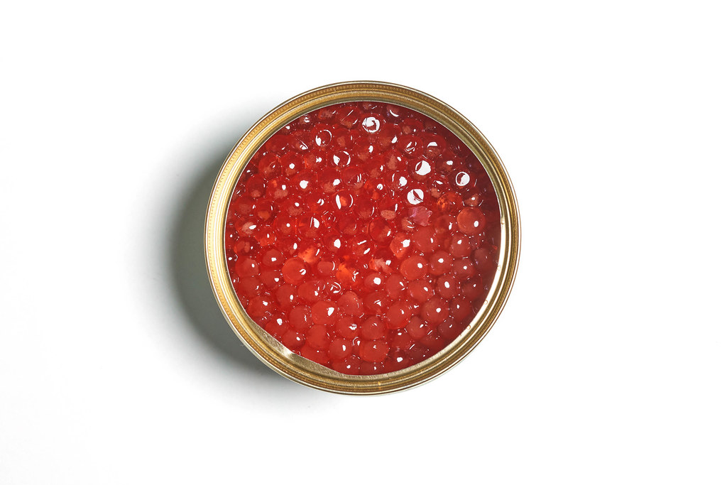 Bowl of red caviar on white