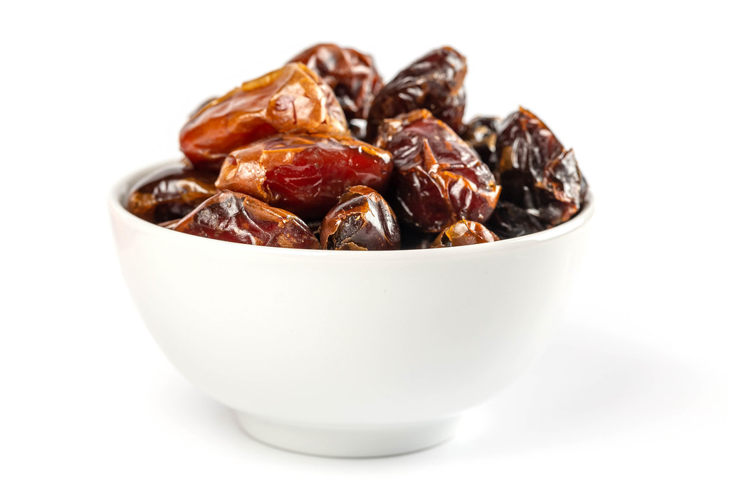 Bowl with dried sweet dates on white
