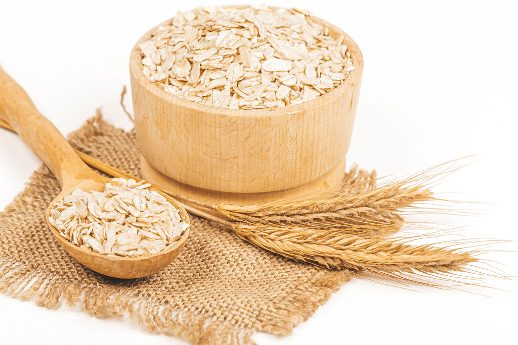 Bowl with raw oatmeal on white background with spikelets