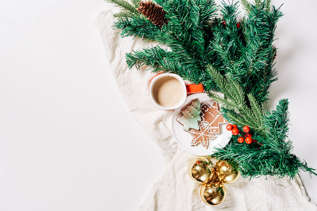 Branch of pine tree, Christmas baubles, cookies and cup of coffee on white background