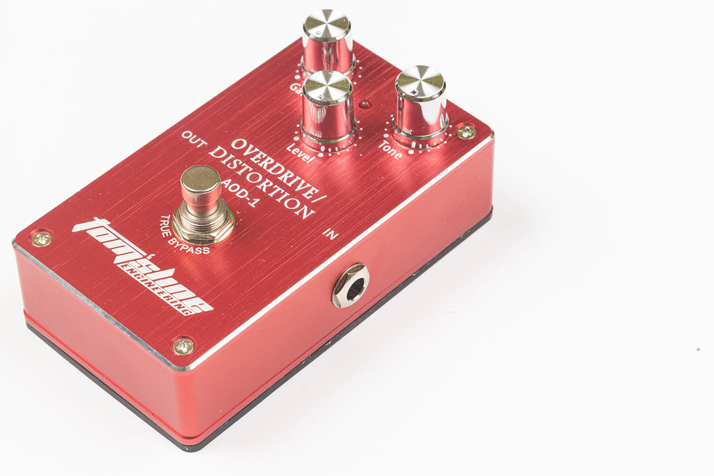 Brand new guitar overdrive and distortion pedal above white background