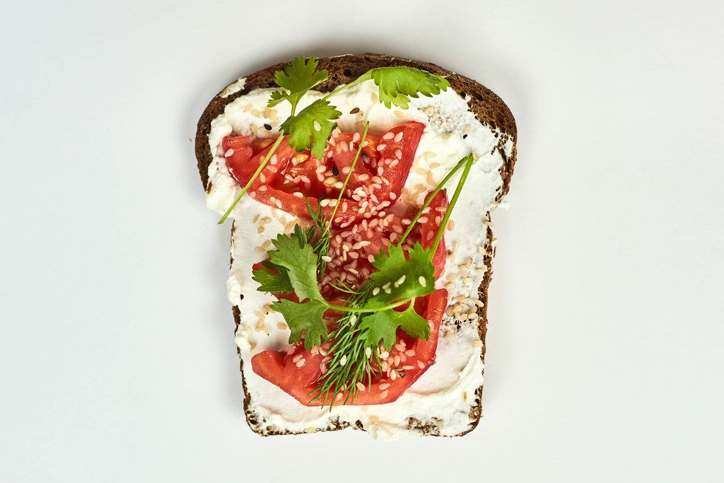 Bread slice with spread sour cream, tomato and parsley