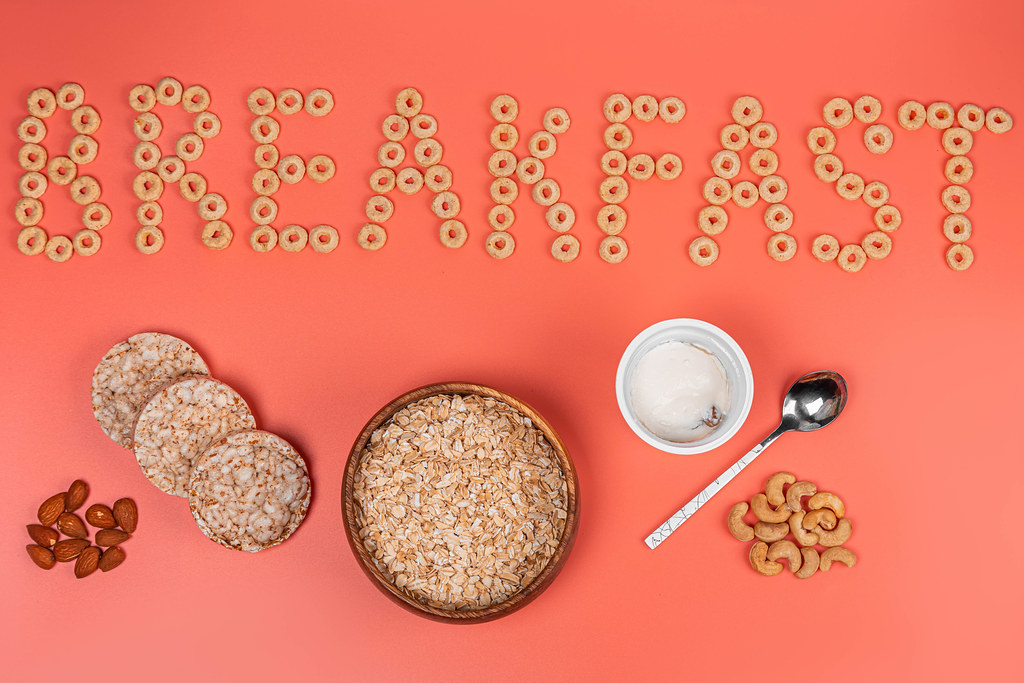 Breakfast background with a bowl of oatmeal, nuts and cottage cheese on a pink background