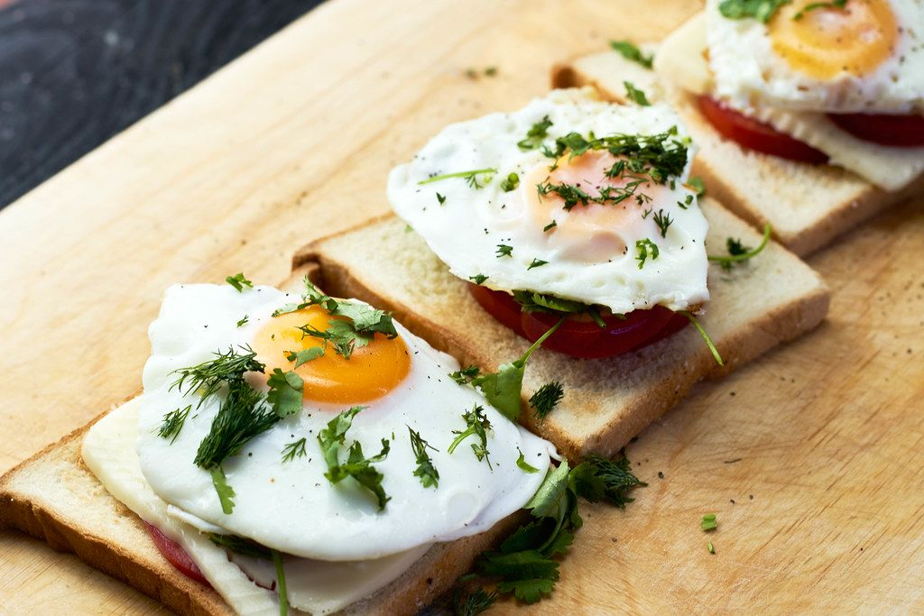 Breakfast for three people at home, fried eggs with toast, mozzarella and tomatoes