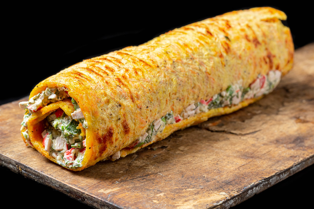 Breakfast roll-ups with omelet, crab sticks and herbs