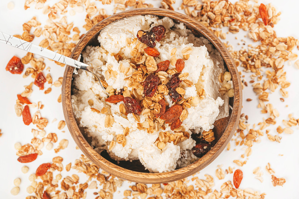 Breakfast with cottage cheese, dried berries and oatmeal on a white background