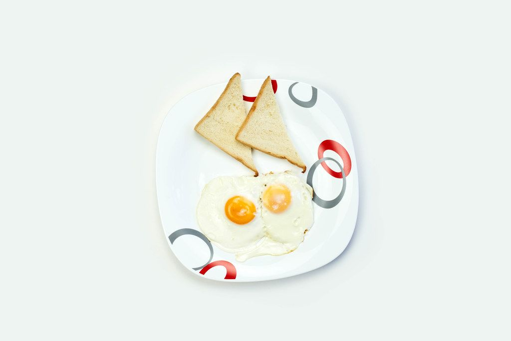 Breakfast with eggs and toasts on white table