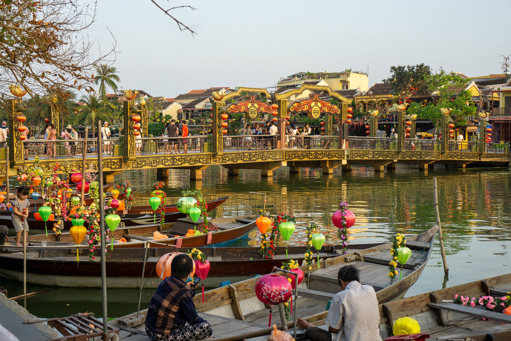 Bridge of Light crossing the Thu Bon River with many Tourist Boats decorated with colorful Lanterns in the Ancient Town of Hoi An, Vietnam