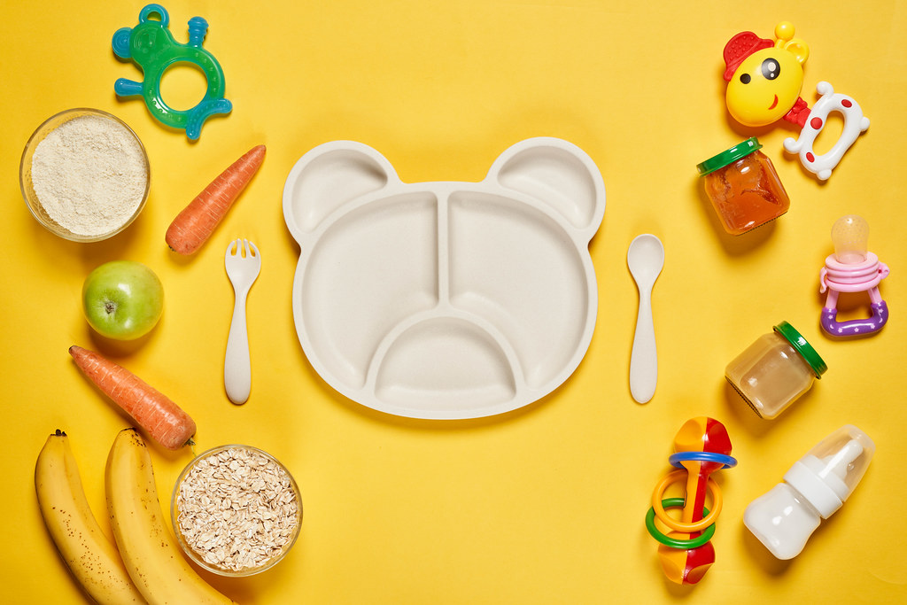 Bright background of baby bamboo plate and pile of toys with various organic baby food