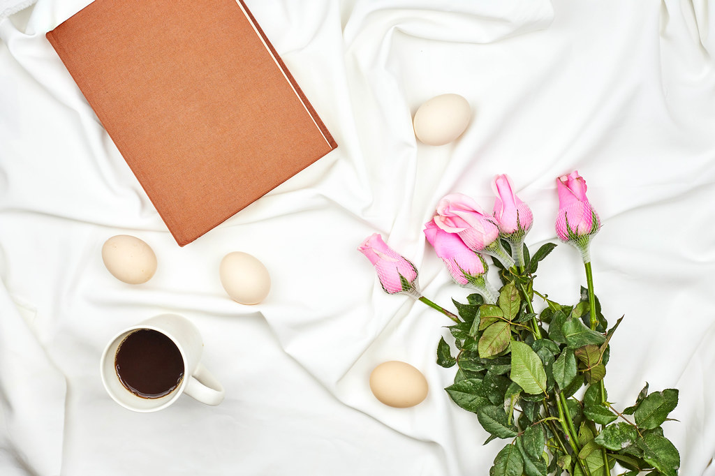 Bright spring background with easter eggs, rose flowers and a cup of coffee