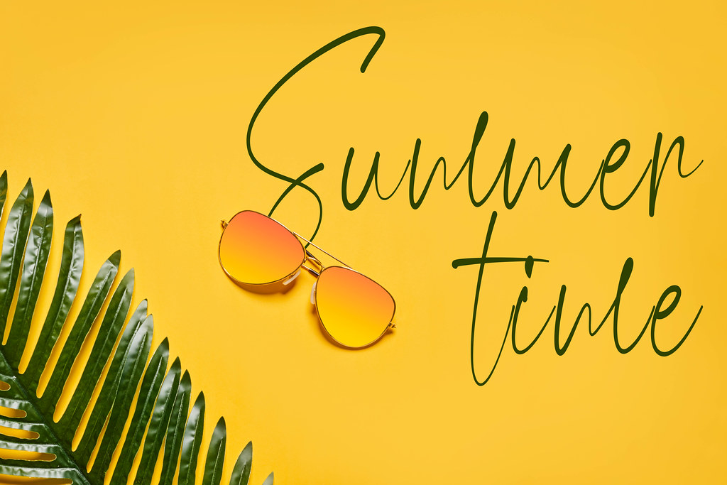 Bright summer background with sunglasses and palm leaf
