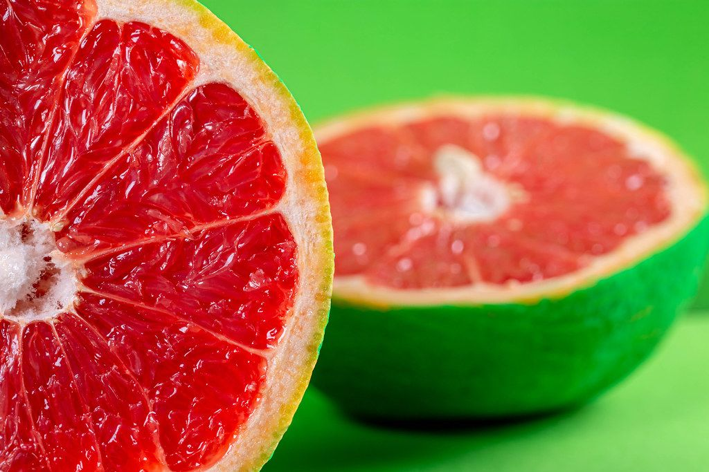 Bright summer fruit background with grapefruit halves on green backdrop