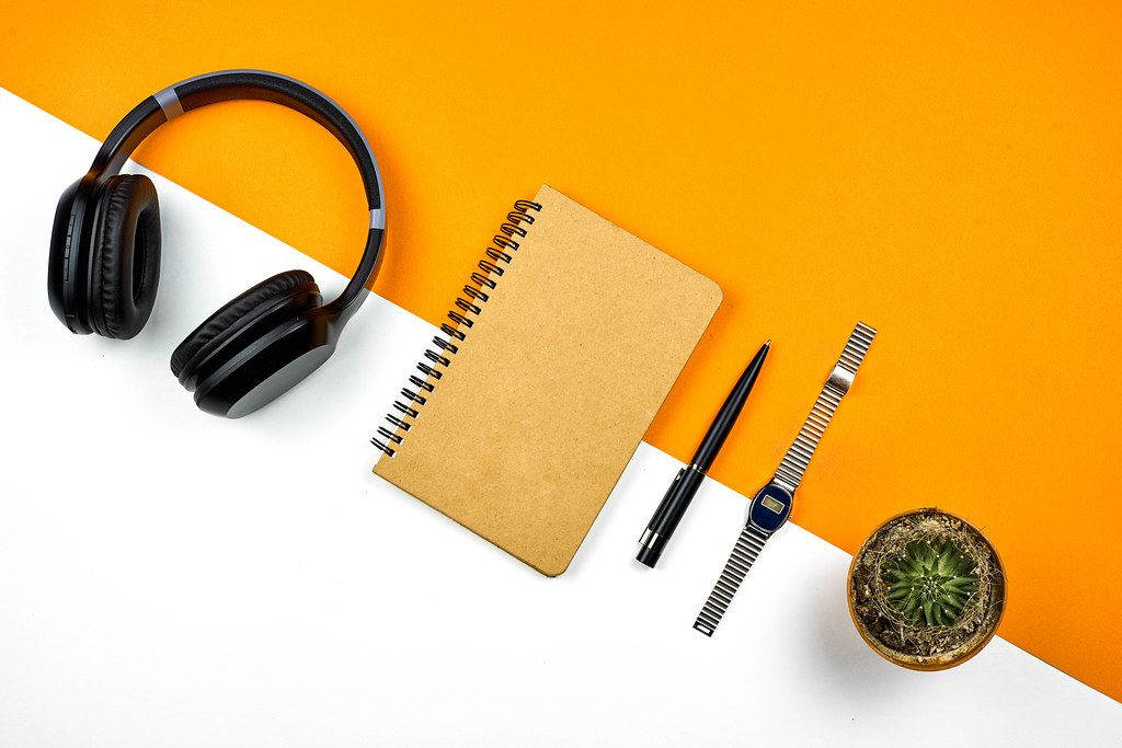 Bright workspace. Wireless headphone, notepad, wristwatch and cactus from above