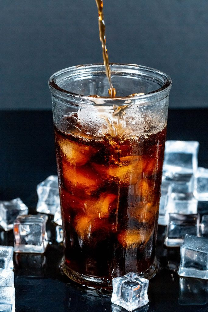 Brown carbonated drink is poured into a glass with ice