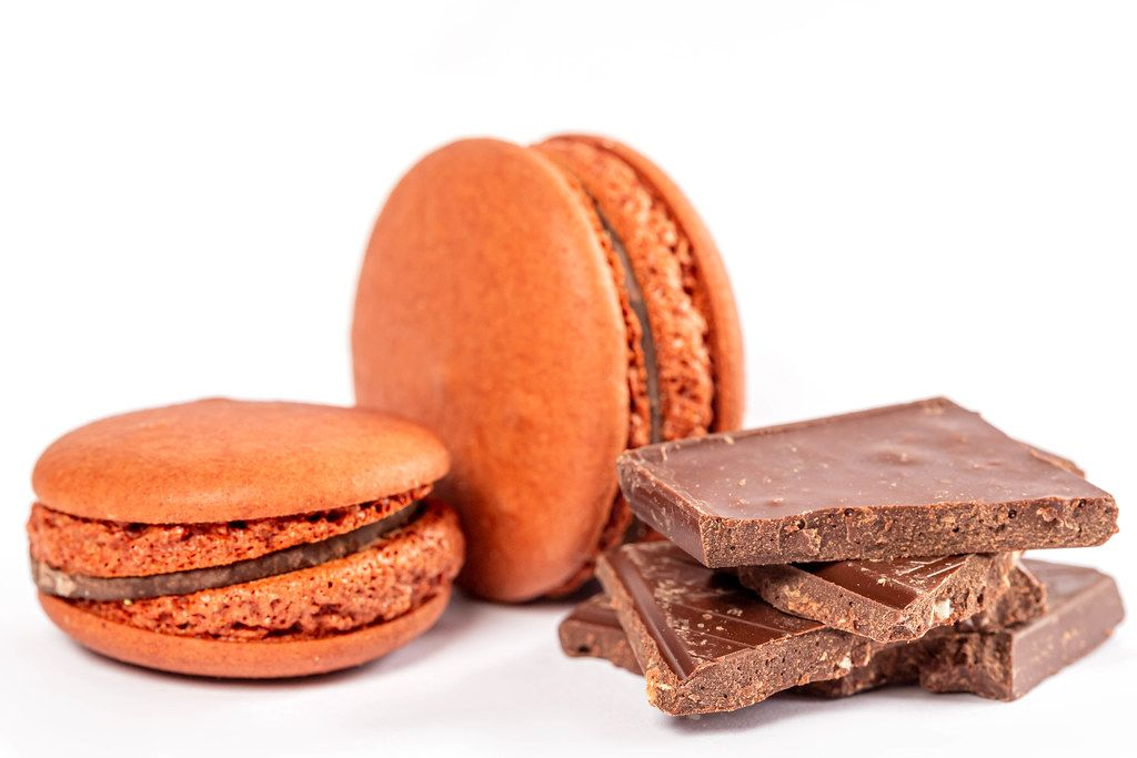 Brown macaroon dessert with chocolate pieces on a white background