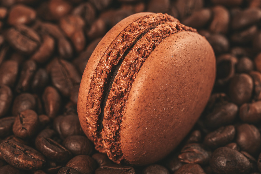 Brown macaroon on a background of coffee beans