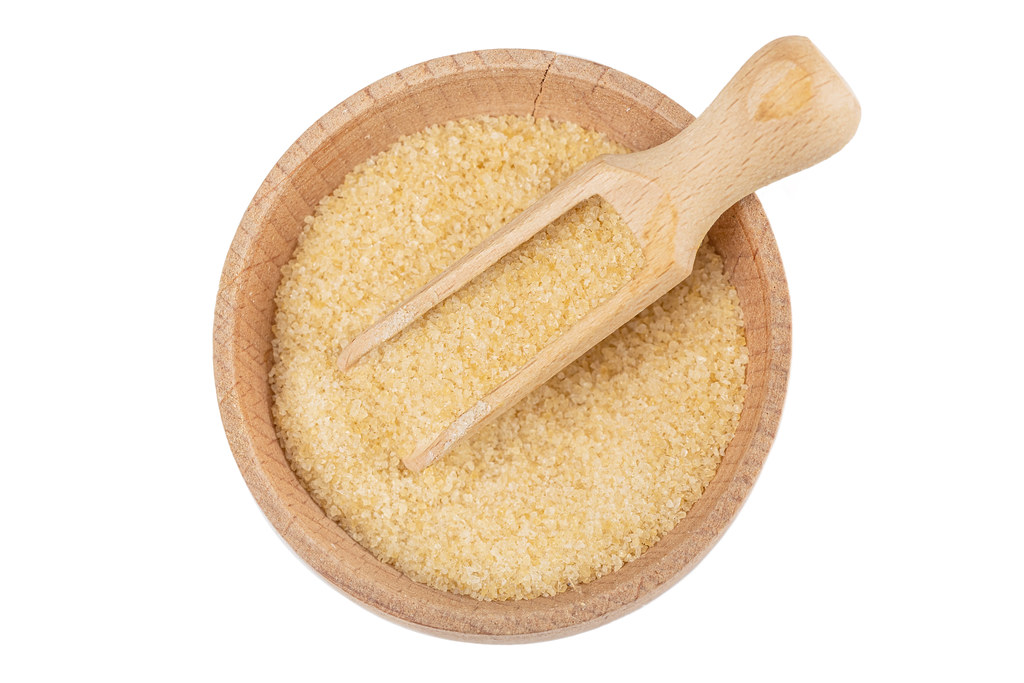 Brown sugar in a wooden bowl with a scoop, top view