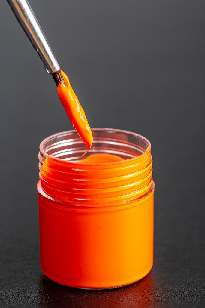 Brushes with orange paint with a jar of gouache paint on a dark background