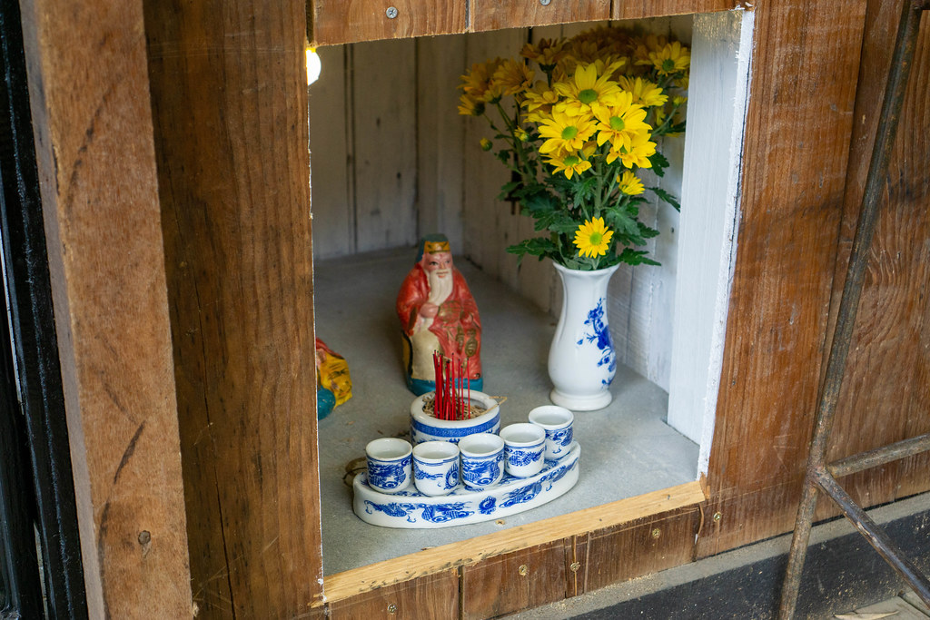 Buddhist Shrine with Flowers, Liquor in Ceramic Cups and a Small Statue of the God of Money at a Cafe in Vietnam