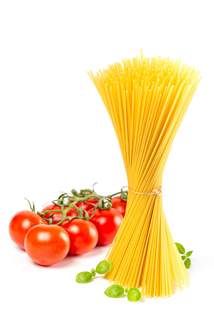 Bunch of dry spaghetti with fresh tomatoes on white background