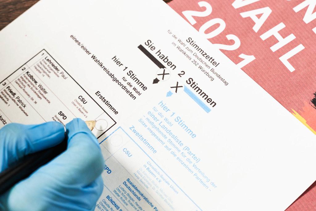 Bundestagswahl 2021: Hand eines Wählers mit Einmalhandschuh wählt für die CSU als Erststimme