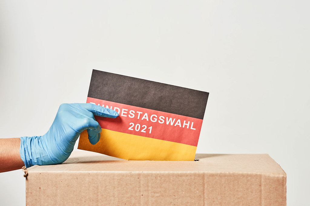 Bundestagswahl 2021 in Corona-Zeiten: Hand mit Einmalhandschuh, deutsche Flagge und Wahlurne