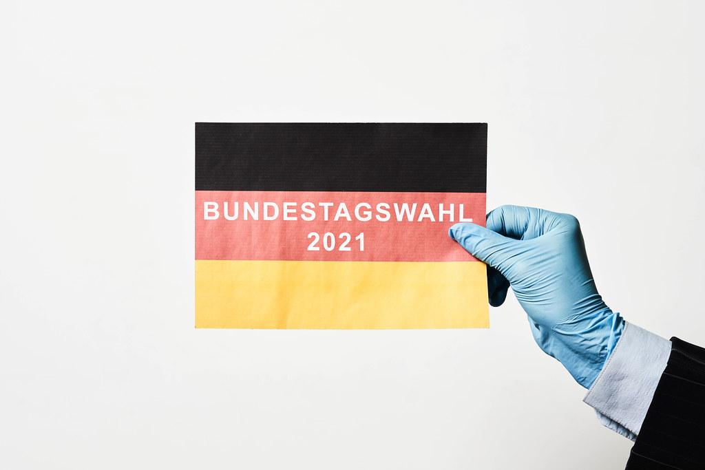 Bundestagswahl 2021: Schrift auf der deutschen Flagge mit Einmalhandschuh gehalten