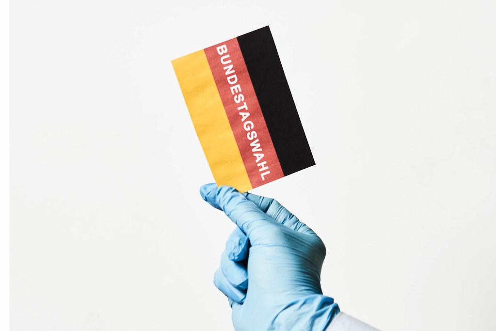 Bundestagswahl in der Corona-Pandemie: Hand mit Einmalhandschuh hält Zettel mit deutscher Flagge