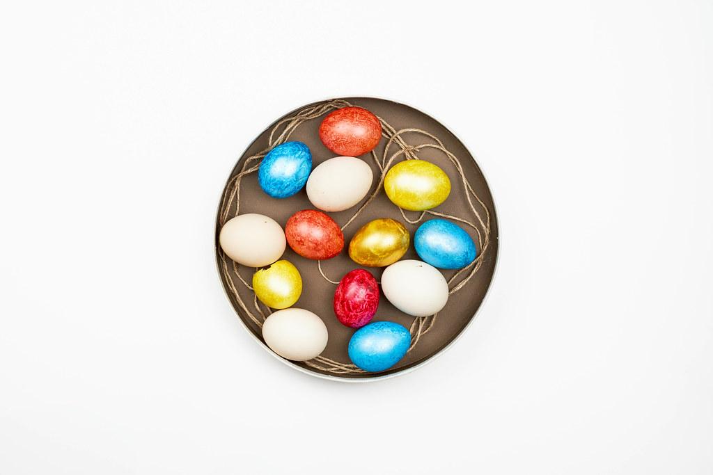 Bunte Eier zu Ostern auf einem braunen Teller vor weißem Hintergrund. Aufnahme von oben