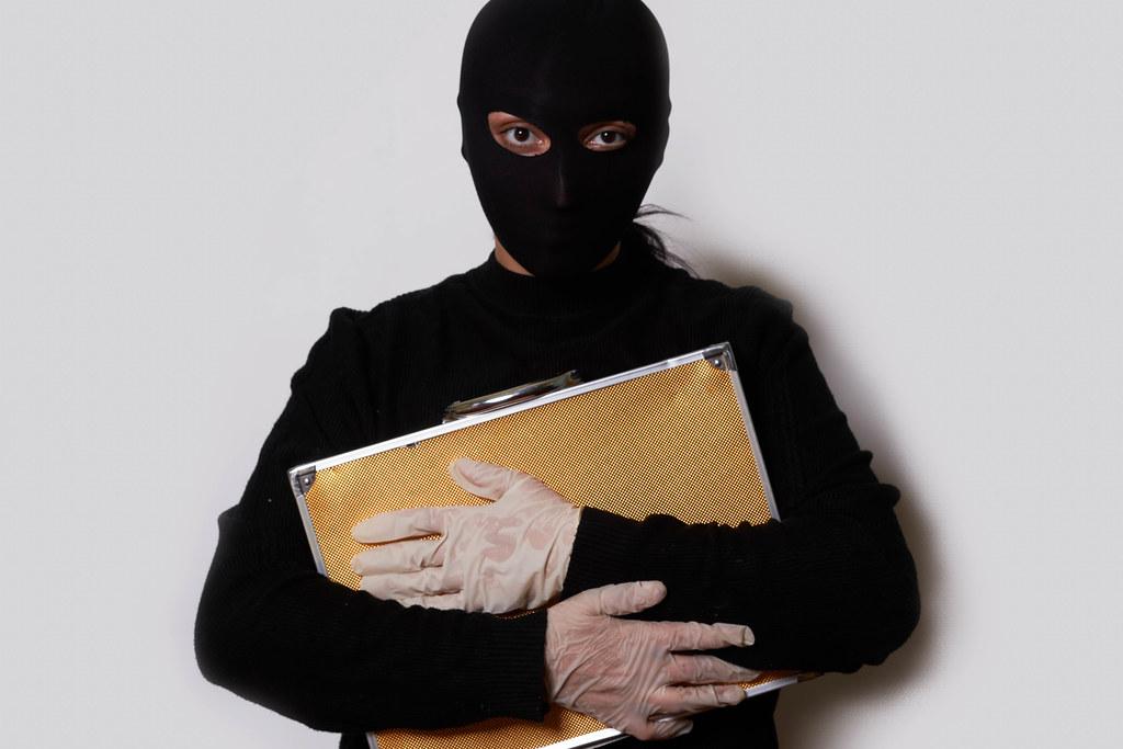 Burglar holding a bag full of money and gems