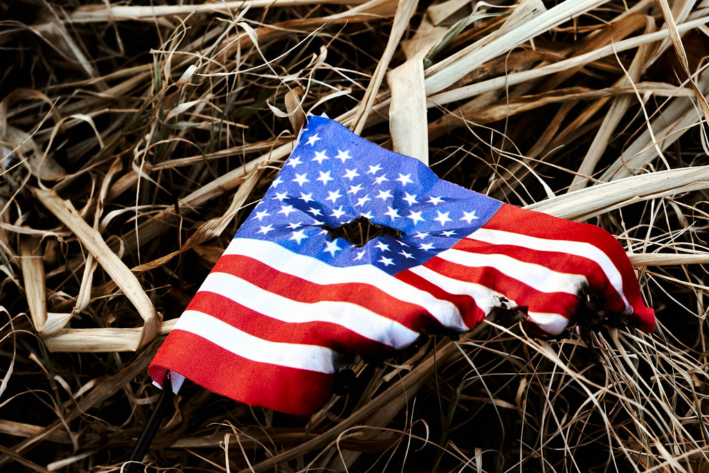 Burned american flag left in the dirt after riots at the capitol hill