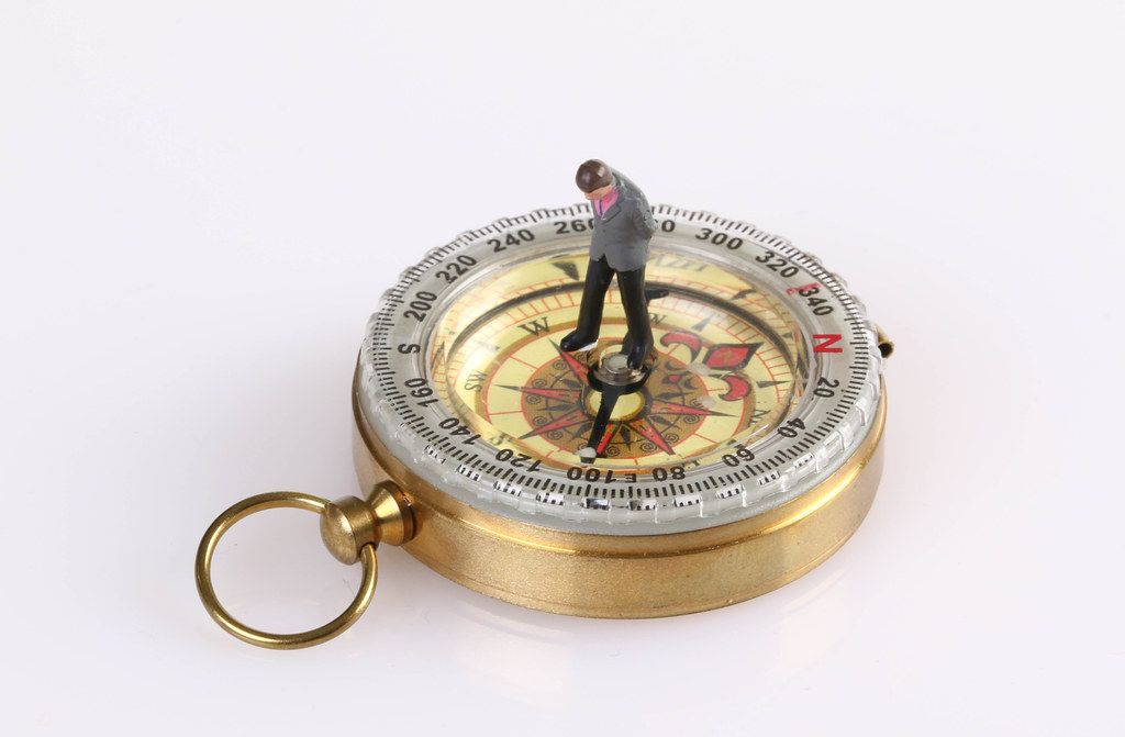 Businessman figure standing on compass