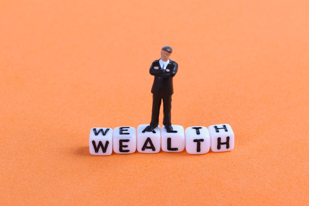 Businessman figure standing on Wealth text