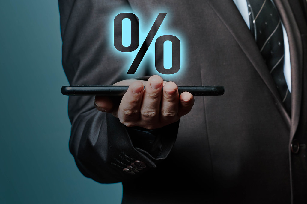 Businessman holding tablet with percent icon