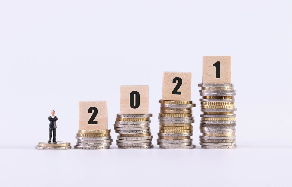 Businessman, stack of coins and wooden cubes with 2021 text