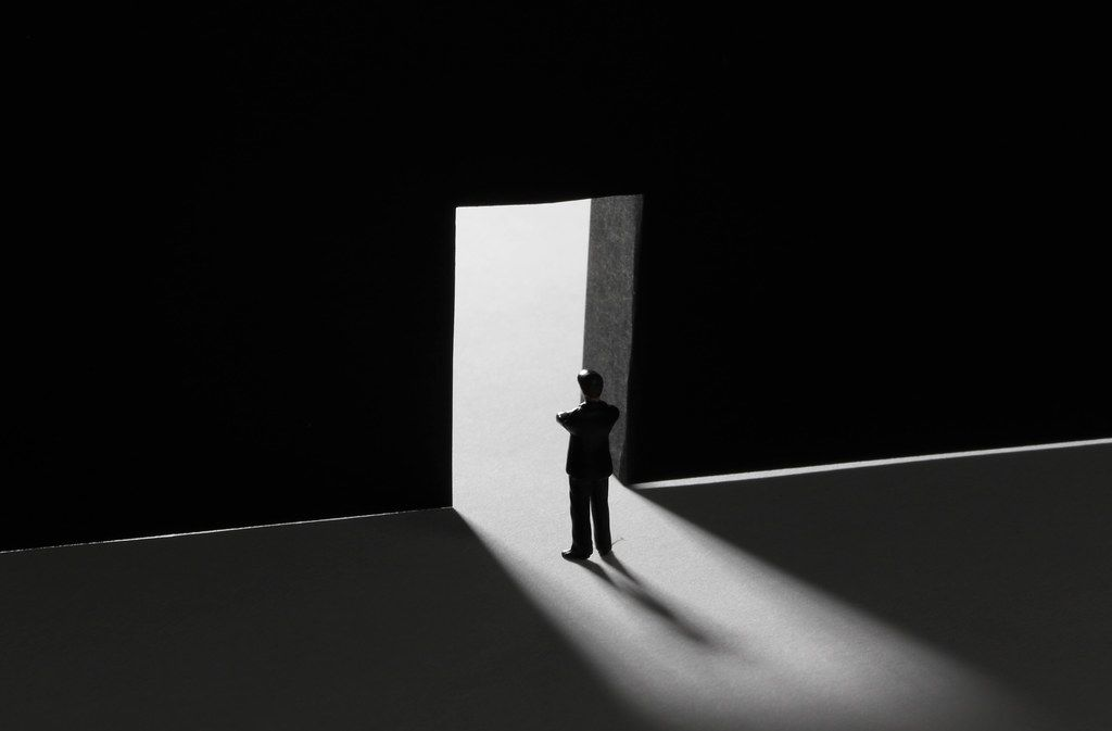Businessman standing alone in front of a big doors
