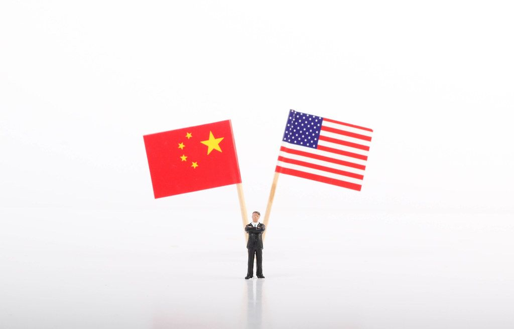 Businessman standing in front of flags of China and USA