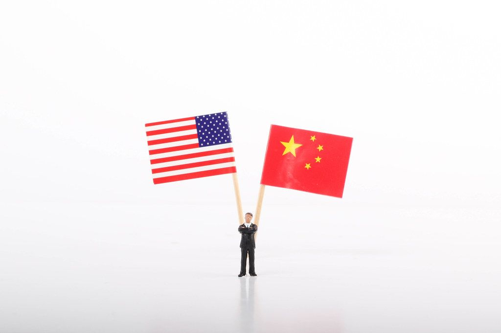 Businessman standing in front of flags of USA and China