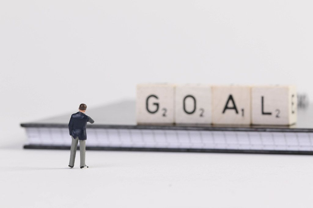 Businessman standing in front of Goal text