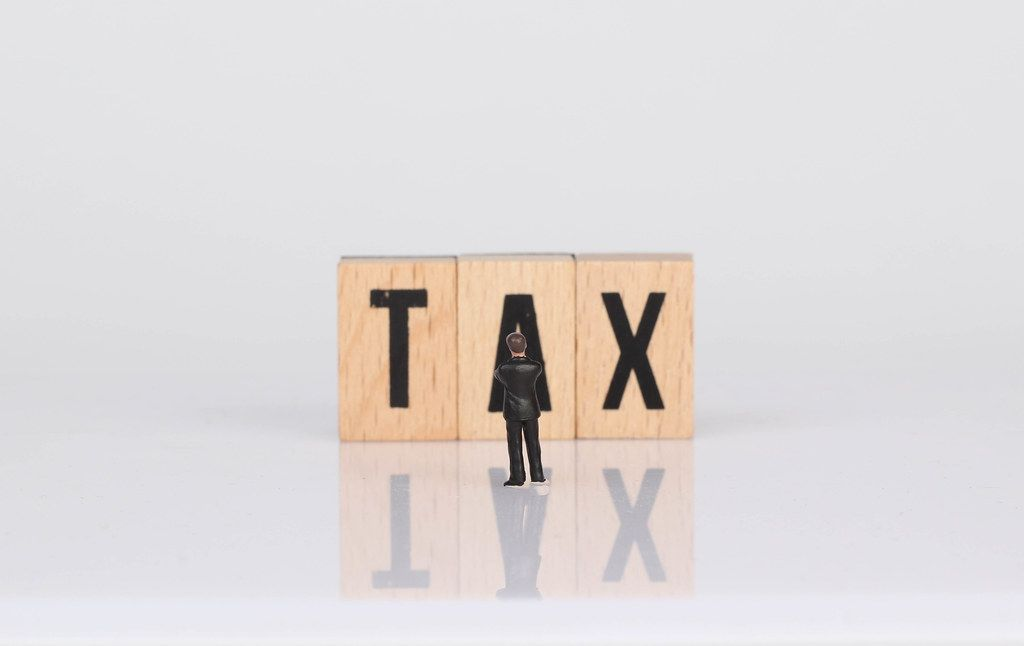 Businessman standing in front of Tax text